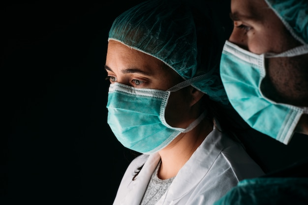 Zakończenie dwa bocznej kobiety i samiec lekarki pracuje będący ubranym medyczną maskę chirurgiczną, medyczną nakrętkę i wirusową odzież ochronną na czerni ścianie z kopii przestrzenią. covid-19 pandemia koronawirusa.