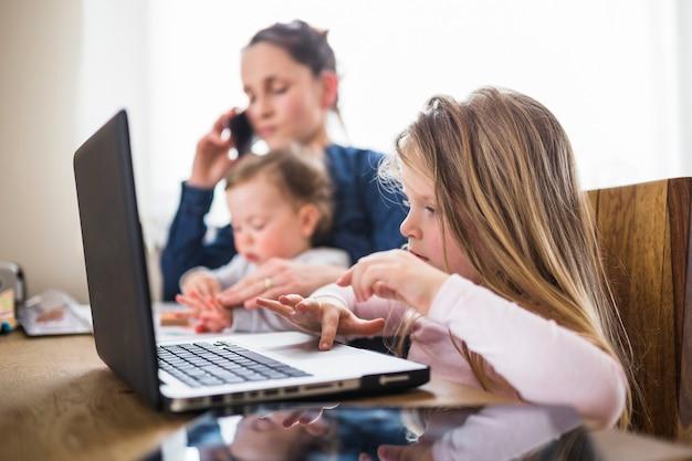 Zakończenie dziewczyna używa laptop nad drewnianym biurkiem