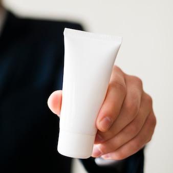 Zakończenie elegancki mężczyzna trzyma up białą kremową butelkę