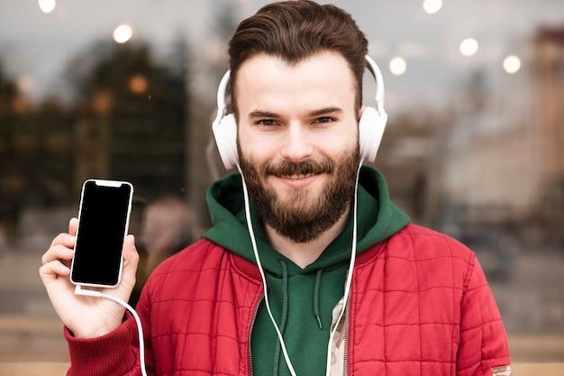 Zakończenie facet trzyma smartphone z hełmofonami