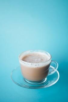 Zakończenie filiżanki kawy latte z błękitnym tłem