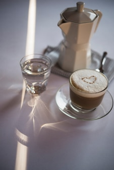 Zakończenie filiżanki kawy latte z czajnikiem