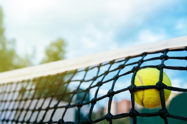 Zakończenie fotografia tenisowej piłki ciupnięcie sieć. pojęcie sportu.