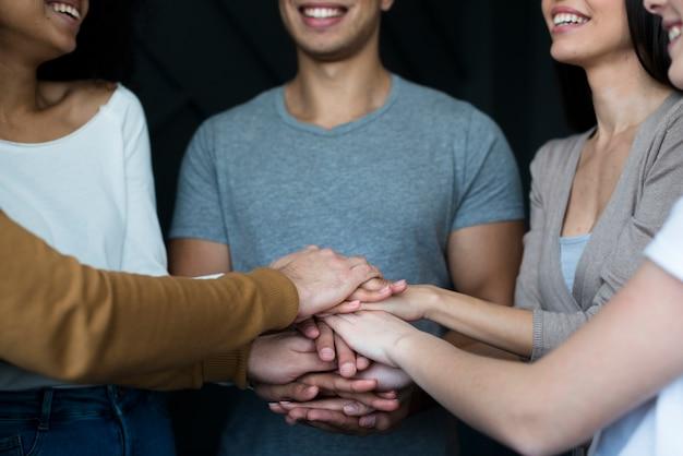 Zakończenie grupa pozytywni ludzie trzyma ręki