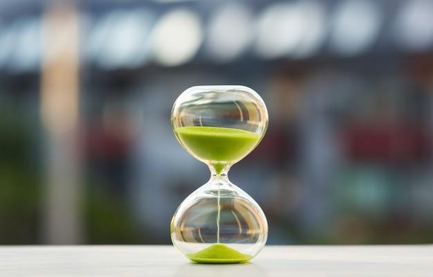 Zakończenie, hourglass z zielonym piaskiem na zamazanym tle