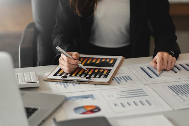 Zakończenie interesu pracująca ręka wskazuje wykres w urzędzie.
