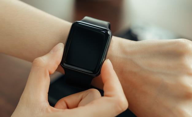 Zakończenie jest ubranym w zegarka zastosowaniu kobieta.