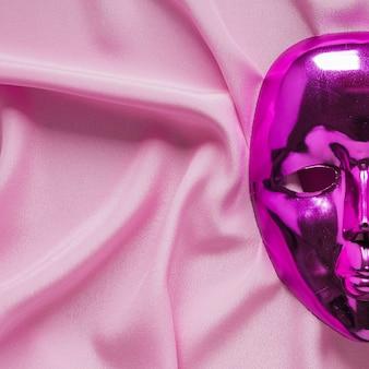 Zakończenie karnawał maska na różowej tkaninie