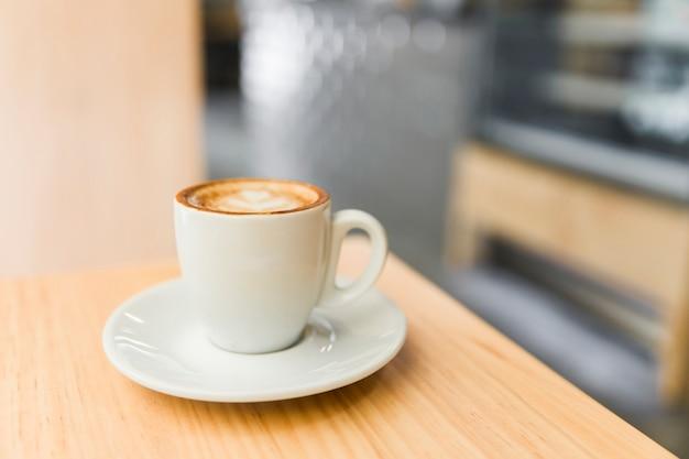 Zakończenie kawowy latte na drewnianym stole