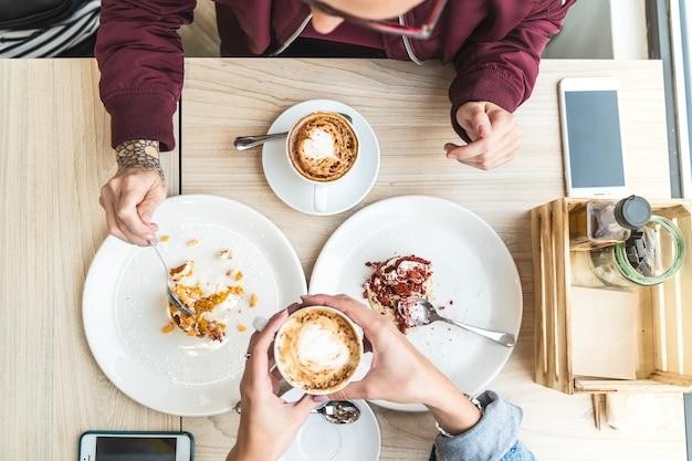 Zakończenie kobiet ręki trzyma gorącego cappuccino w kawiarni up.