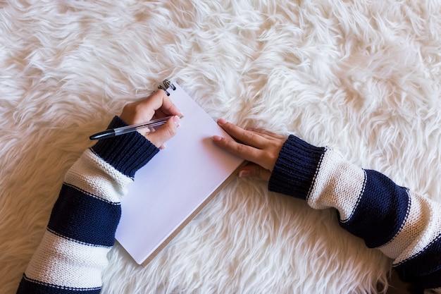 Zakończenie kobiet ręki up pisać na maszynie na telefonie komórkowym. prawa ręka trzyma dzbanek soku pomarańczowego. widok z góry. białe tło.