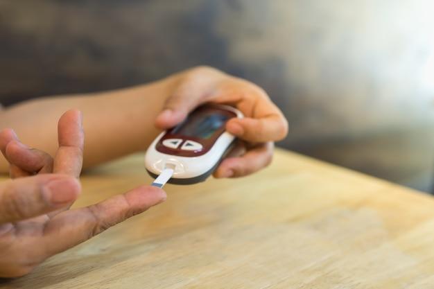 Zakończenie kobiet ręki up używa glukometru na palcu sprawdzać poziom cukru we krwi. użyj jako koncepcji medycyny, cukrzycy, glikemii, opieki zdrowotnej i ludzi.