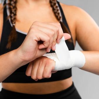Zakończenie kobieta bandażuje jej ręka frontowego widok