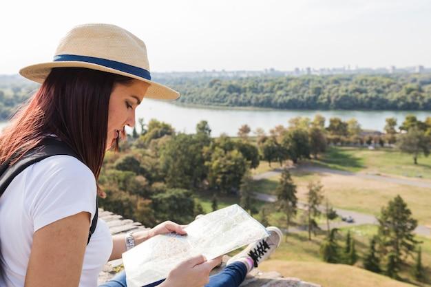 Zakończenie kobieta jest ubranym kapeluszowy patrzeć w mapie przy outdoors
