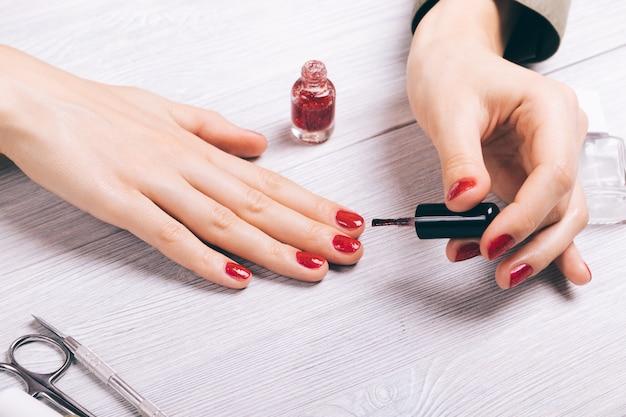 Zakończenie kobieta maluje jej paznokcie czerwonym lakierem