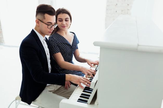 Zakończenie kobieta patrzeje przystojnego mężczyzna bawić się pianino