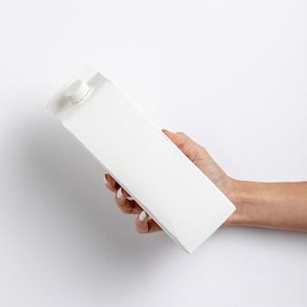 Zakończenie kobieta trzyma białego kartonowego zbiornik