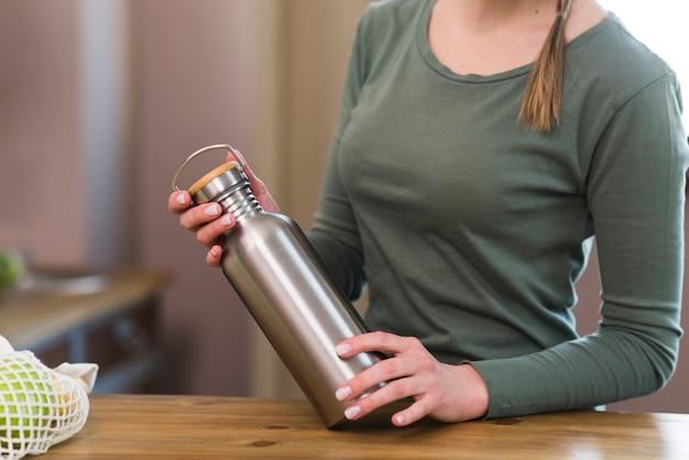Zakończenie kobieta trzyma kawowego termos