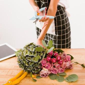 Zakończenie kobieta trzyma kwiatu nożyce