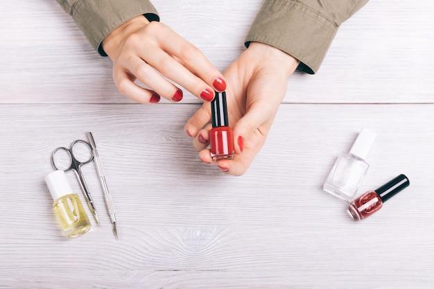 Zakończenie kobieta trzyma manicure czerwoną lakier w rękach