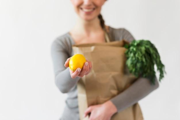 Zakończenie kobieta trzyma papierową torbę z sklepami spożywczymi