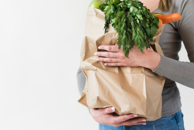 Zakończenie kobieta trzyma papierową torbę z warzywami
