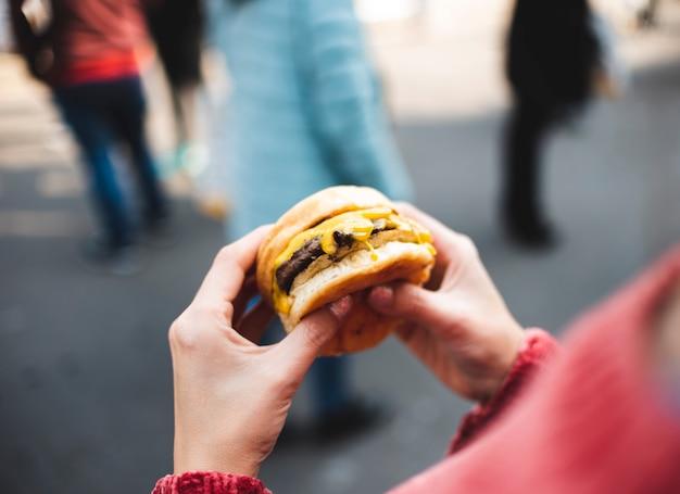 Zakończenie kobieta trzyma smakowitego hamburger