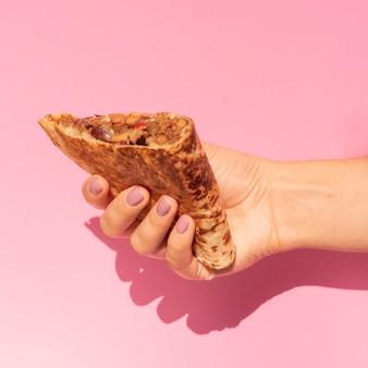 Zakończenie kobieta trzyma smakowitego meksykańskiego jedzenie
