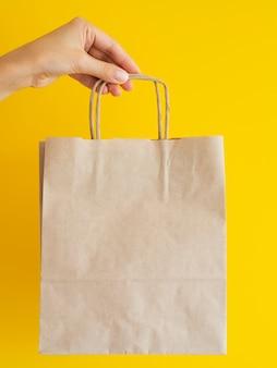 Zakończenie kobieta trzyma up papierową torbę