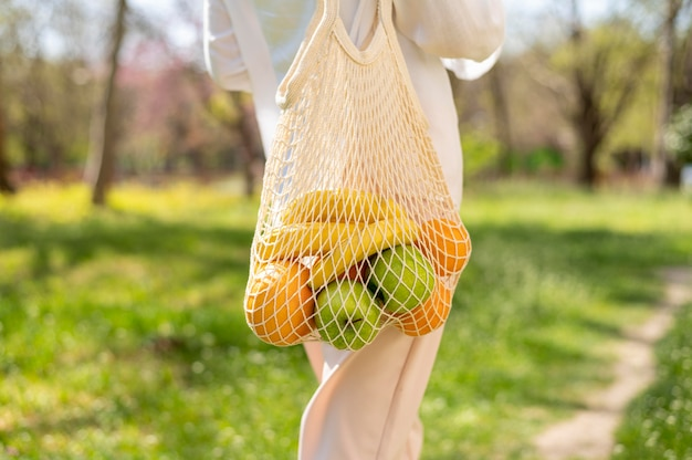 Zakończenie kobieta trzyma wielokrotnego użytku torby chodzącego outside