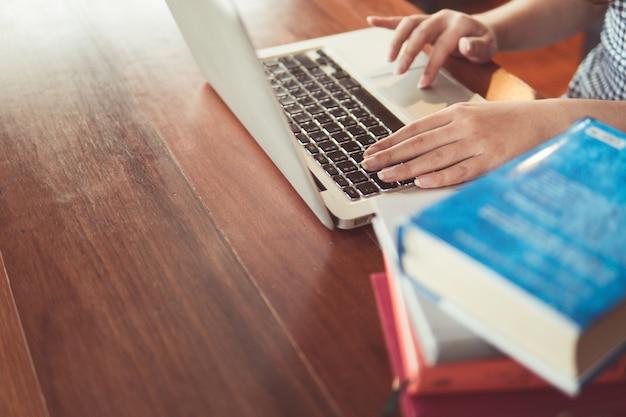 Zakończenie kobieta up wręcza studenckiego obsiadanie przy stołem, writing lub pisać na maszynie na notatniku