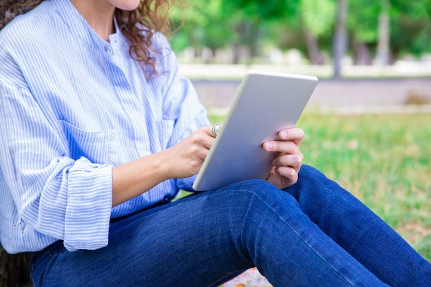 Zakończenie kobieta używa cyfrową pastylkę w lato parku