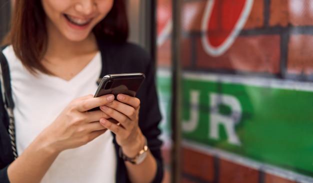 Zakończenie kobieta używa smartphone z pisać na maszynie sms wiadomość przyjaciele
