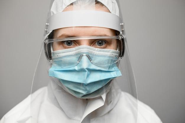 Zakończenie kobieta w ochronnym kostiumu z osłoną i medyczną maską.