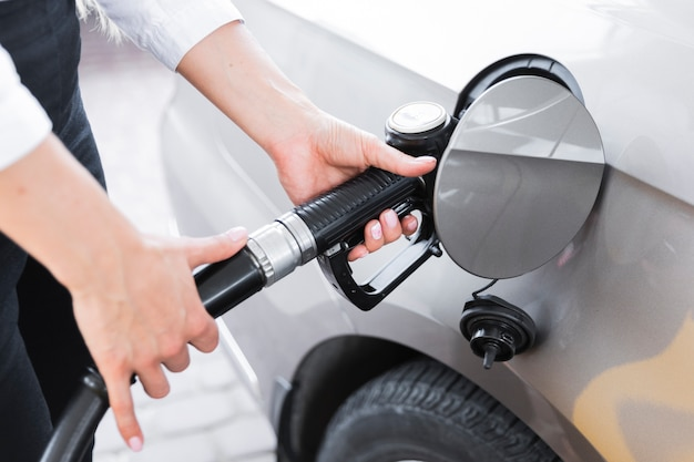 Zakończenie kobieta wypełnia benzynowego zbiornika