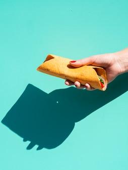 Zakończenie kobieta z burrito i błękitnym tłem