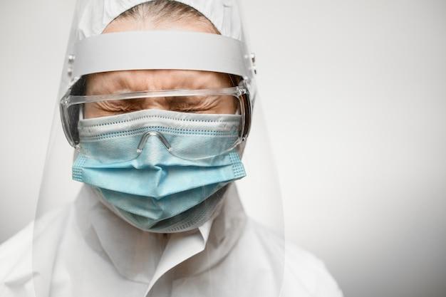 Zakończenie kobiety lekarka z zamkniętymi oczami w kostiumu ochronnym z osłoną i medyczną maską.