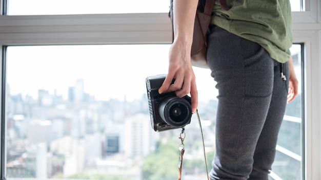 Zakończenie kobiety mienia kamera stoi blisko okno