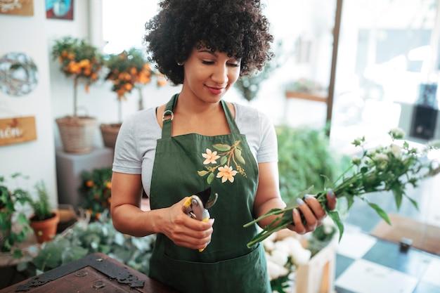 Zakończenie kobiety mienia secateurs i wiązka kwiaty