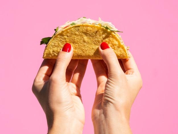 Zakończenie kobiety mienia taco z różowym tłem