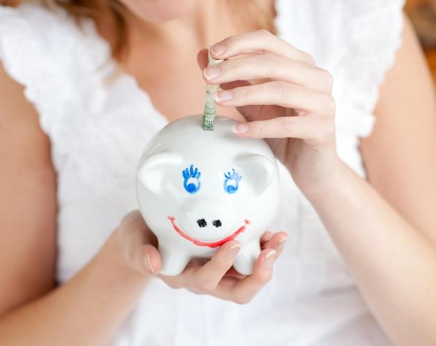 Zakończenie kobiety oszczędzania pieniądze w prosiątku