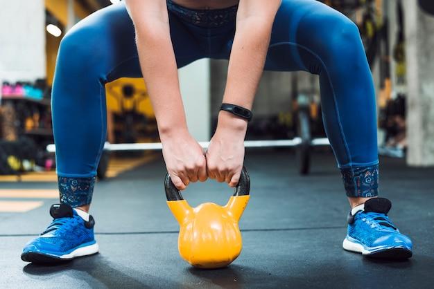 Zakończenie kobiety ręka robi ćwiczeniu z czajnik piłką