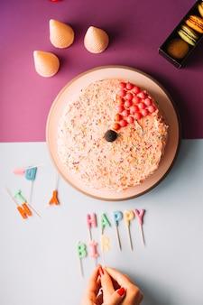 Zakończenie kobiety ręka układa urodzinowe świeczki na podwójnym tle