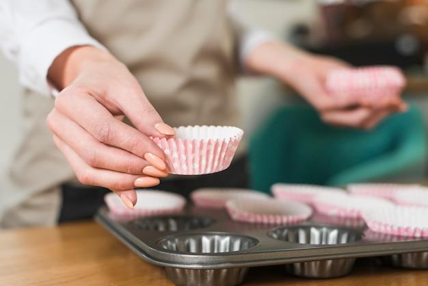 Zakończenie kobiety ręka umieszcza papierowe filiżanki w niecce muffin