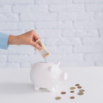 Zakończenie kobiety ręka wkłada pięćdziesiąt euro banknot w piggybank na biurku