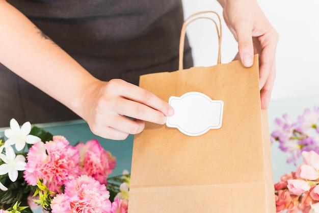 Zakończenie kobiety ręki klejenia etykietka na papierowej torbie