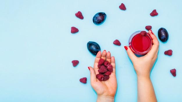 Zakończenie kobiety ręki mienia malinki i sok z śliwkami na błękitnym tle