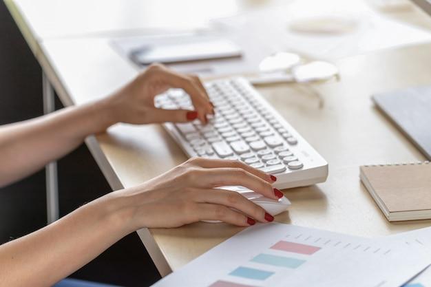 Zakończenie kobiety siedzi pracować przy biurkiem