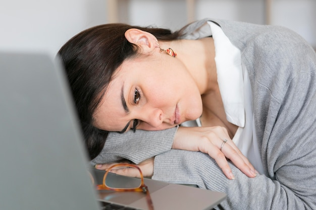 Zakończenie kobiety sleepig na szkło stole blisko laptopu