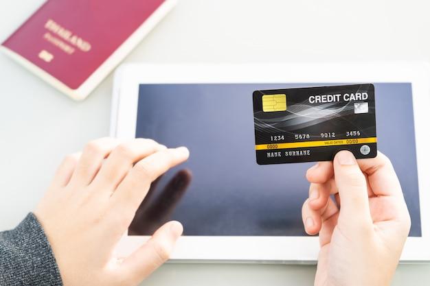 Zakończenie kobiety up wręcza trzymać kredytową kartę z pastylka komputerowym pustym ekranem